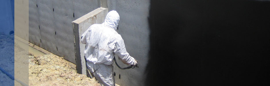 waterproofing being sprayed onto the foundation of a house